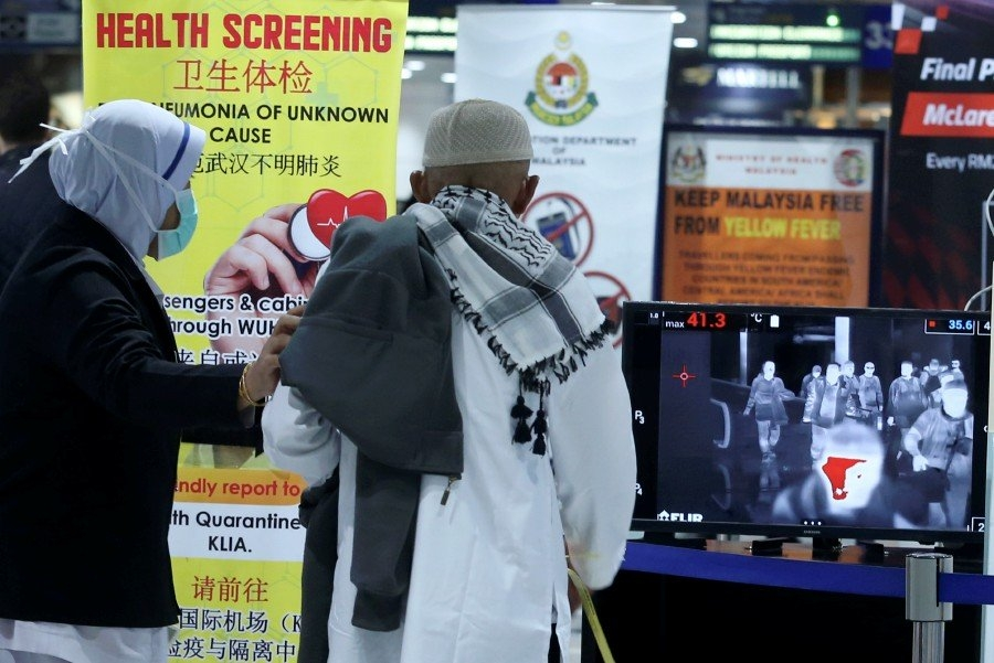Malaysian Health Ministry staff using a thermal scanner to scan passengers arriving at the Kuala Lum ...